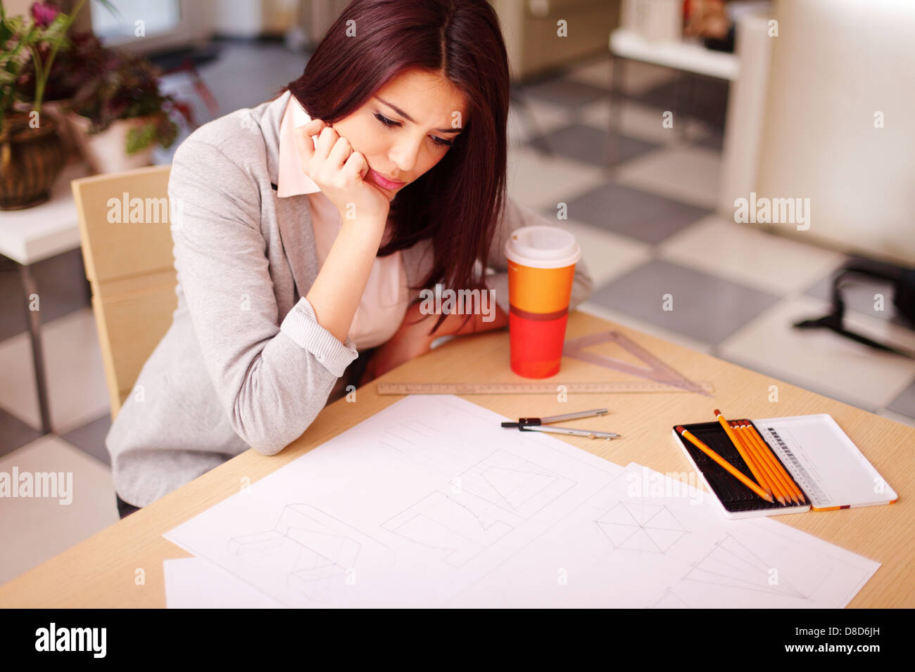 Pensive young architect having a problem with her technical drawings - Stock Image