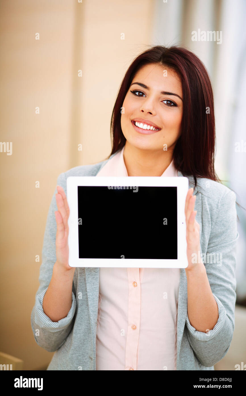 Young beautiful businesswoman showing ipad where you can put your image or text - Stock Image