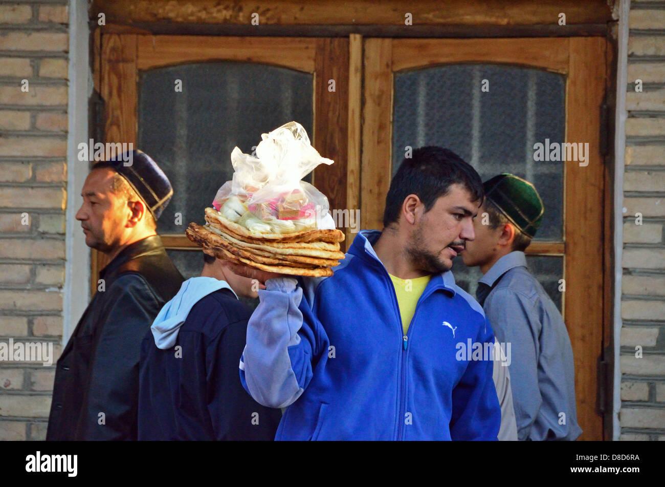 Uzbek man selling bred (lepyoshka) in Bukhara after the ramadan - Stock Image