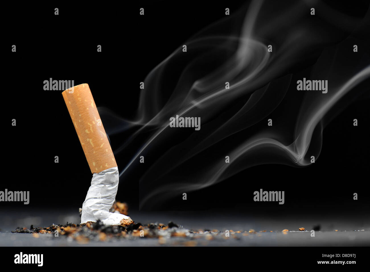 A burning cigarette with smoke against a black background. - Stock Image