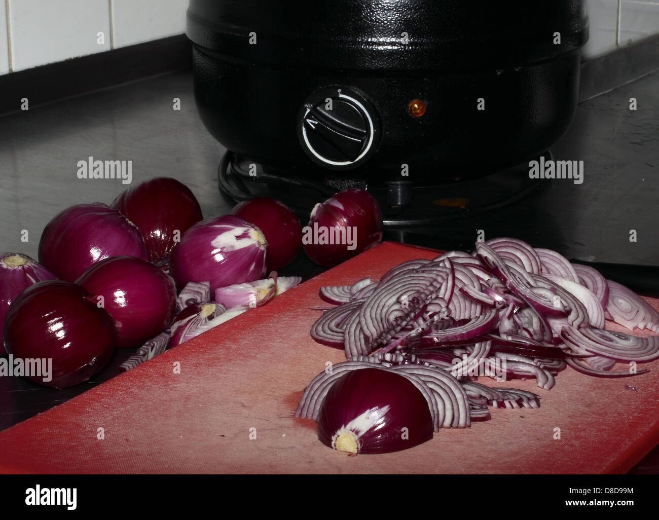 Whole red onions lying on a steel table next to a soup cooker. In front a red plastic cutboard with sliced red onions - Stock Image