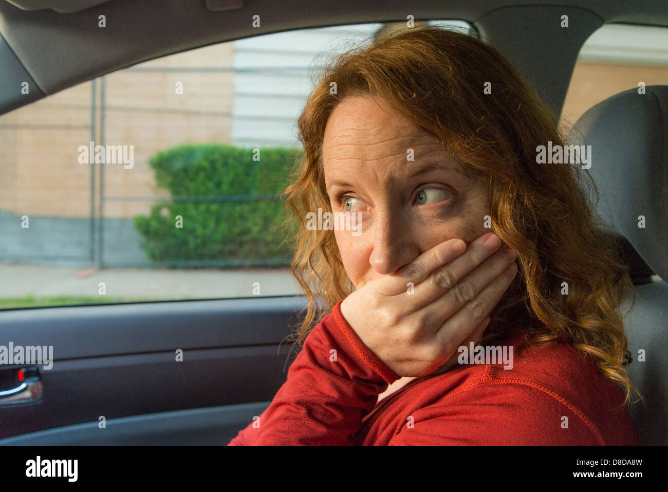 Embarrassed woman's expression after car incident - Stock Image