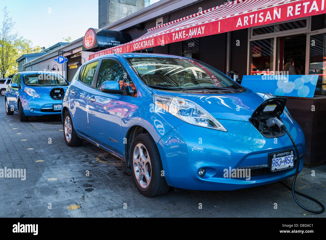 Nissan Electric car at plug in parking stall, Granville Island, Vancouver, British Columbia, Canada - Stock Image