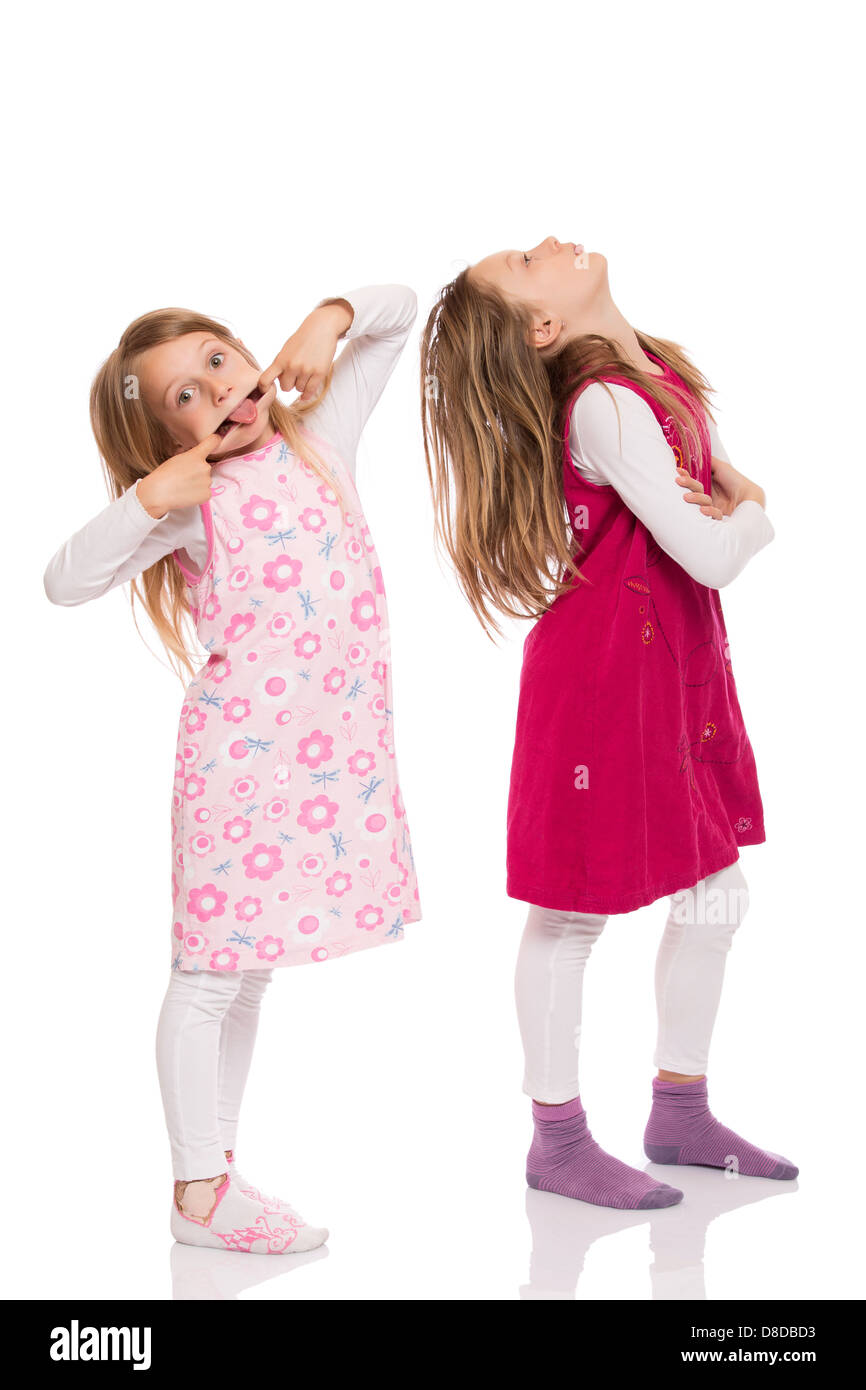Two funny children with long hair making faces. Isolated on white background. - Stock Image