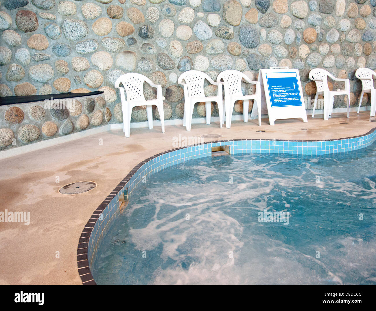Public indoor hot tub with chairs and rules posted - Stock Image