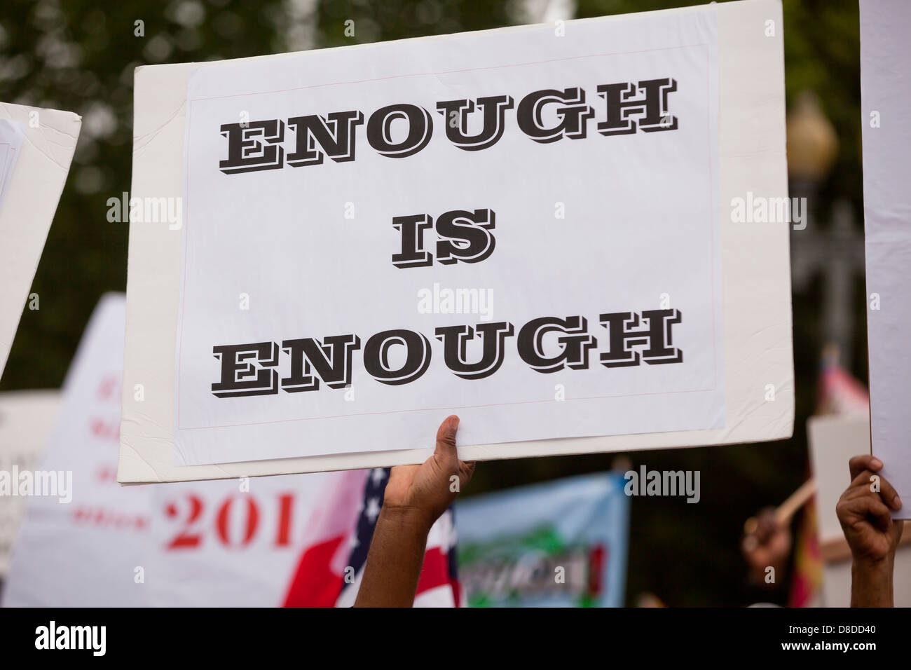 Man holding up an 'Enough is Enough' sign during protest - Stock Image