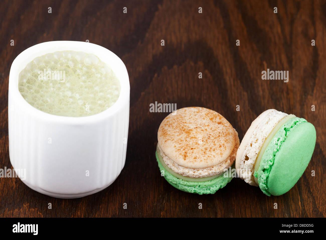 Matcha latte made with almond milk and apple cinnamon macarons - Stock Image