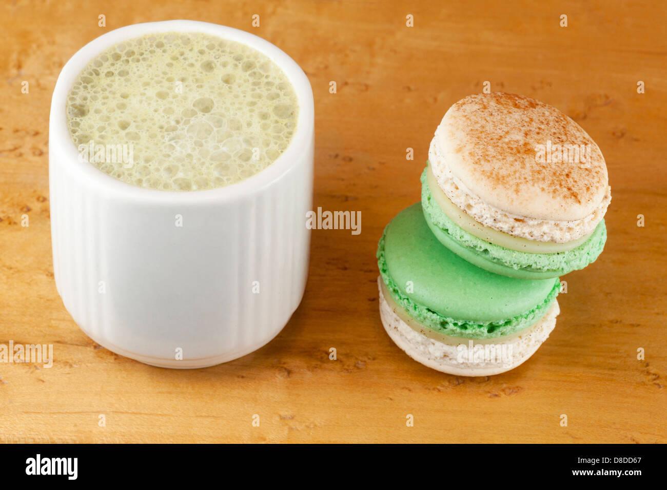Matcha latte made with almond milk, and apple-cinnamon macarons - Stock Image