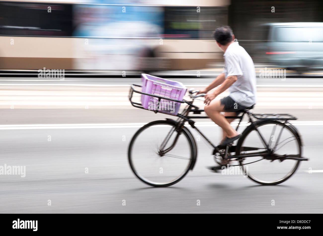 Delivery man riding his bike along Hennessey Road, Hong Kong Island - Stock Image