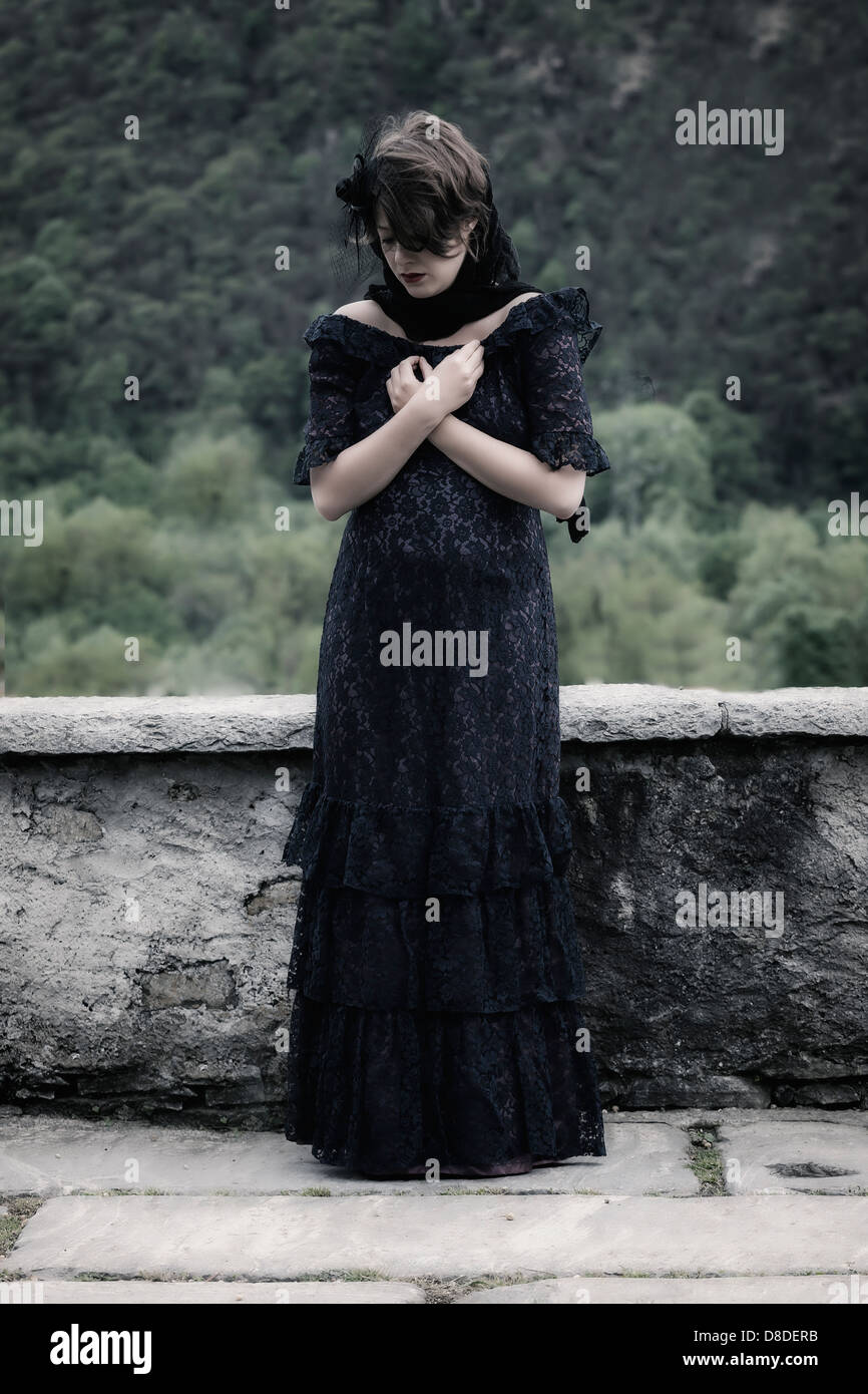 a grieving woman with veil and dark dress, praying - Stock Image