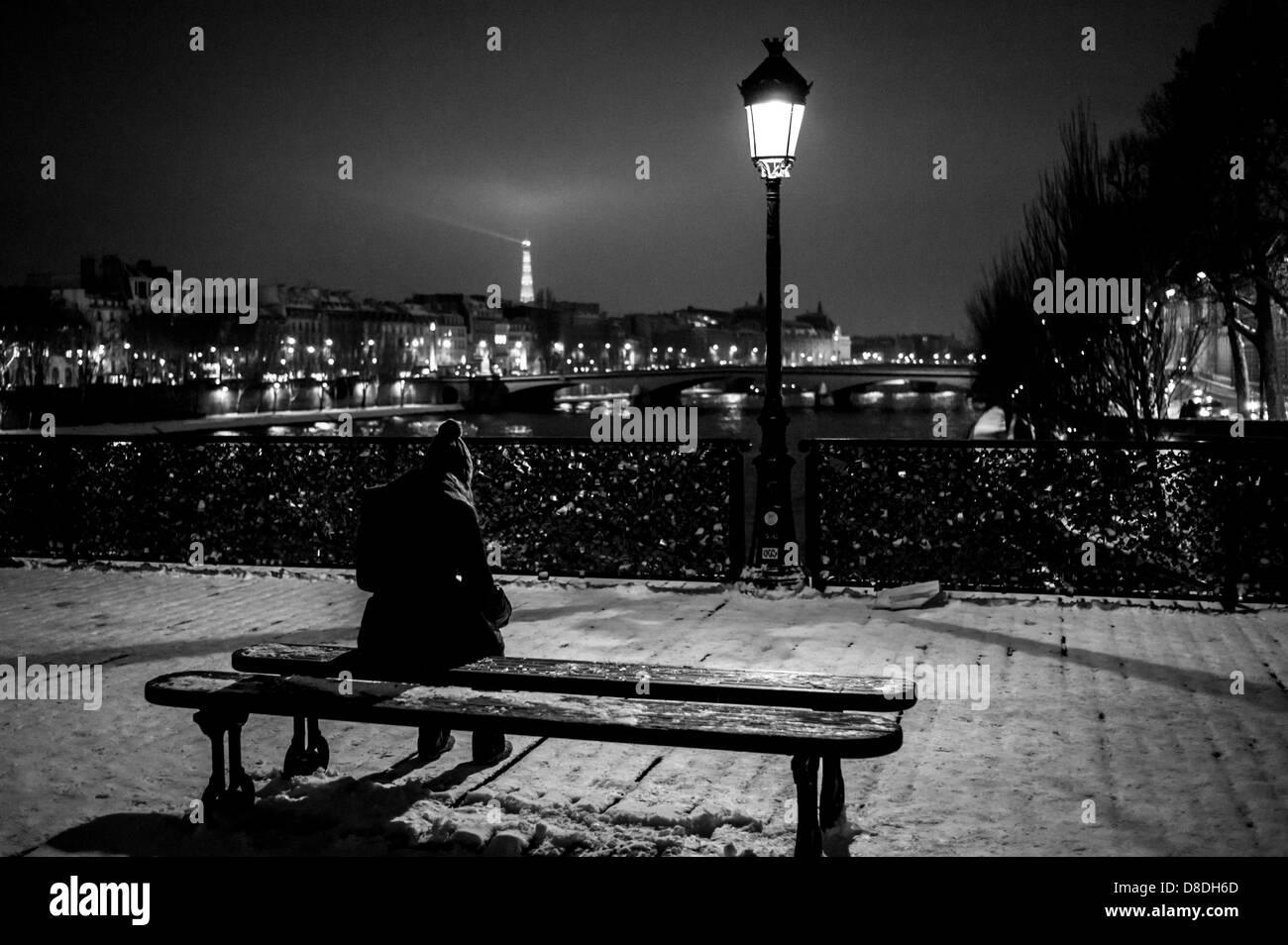 Person sitting alone on a Paris bridge at night. - Stock Image