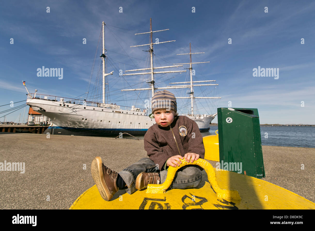 Young boy, 2 years, in front of a square-rigged ship in a harbour - Stock Image