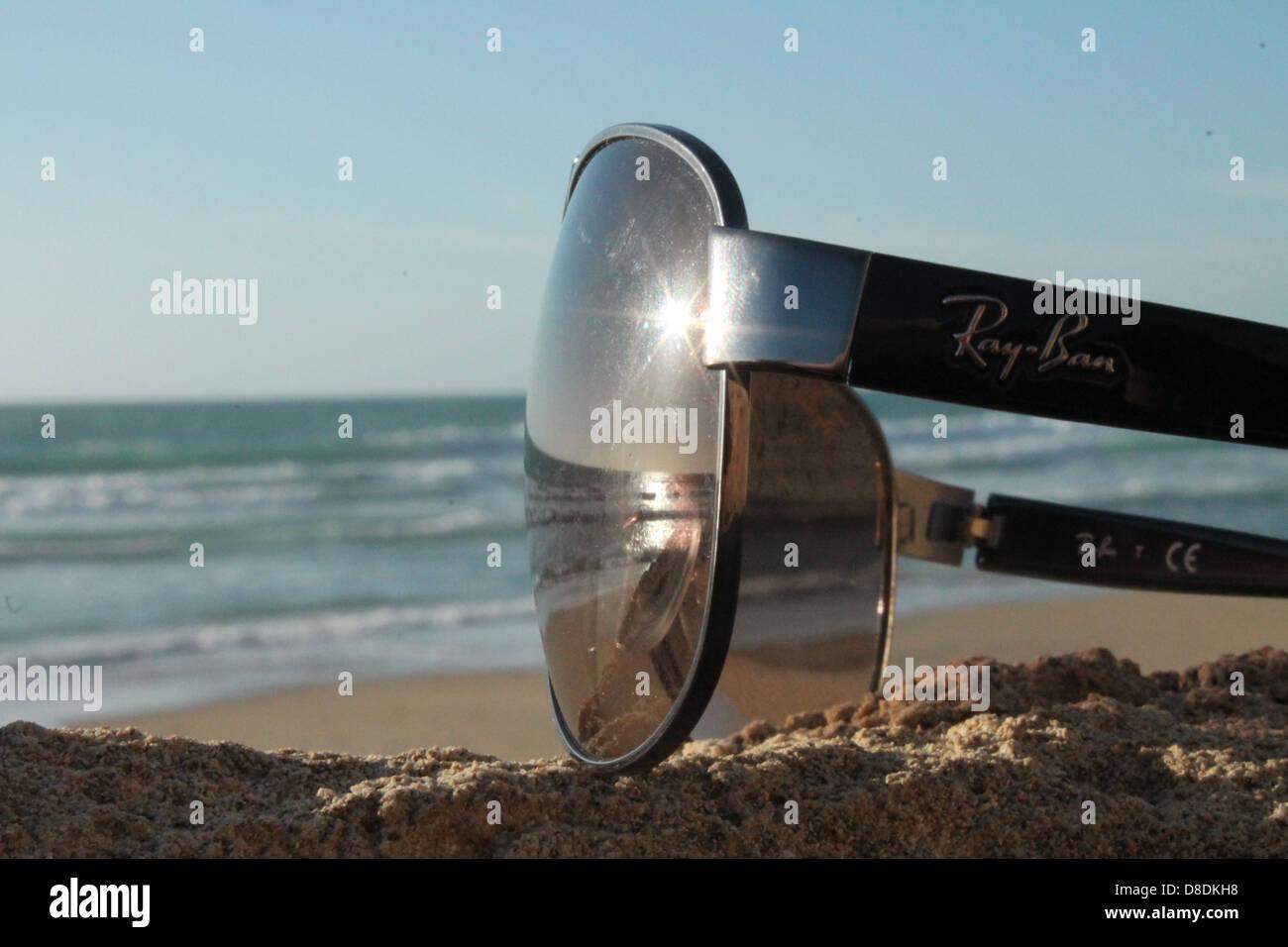 ray ban sunglass beach water - Stock Image