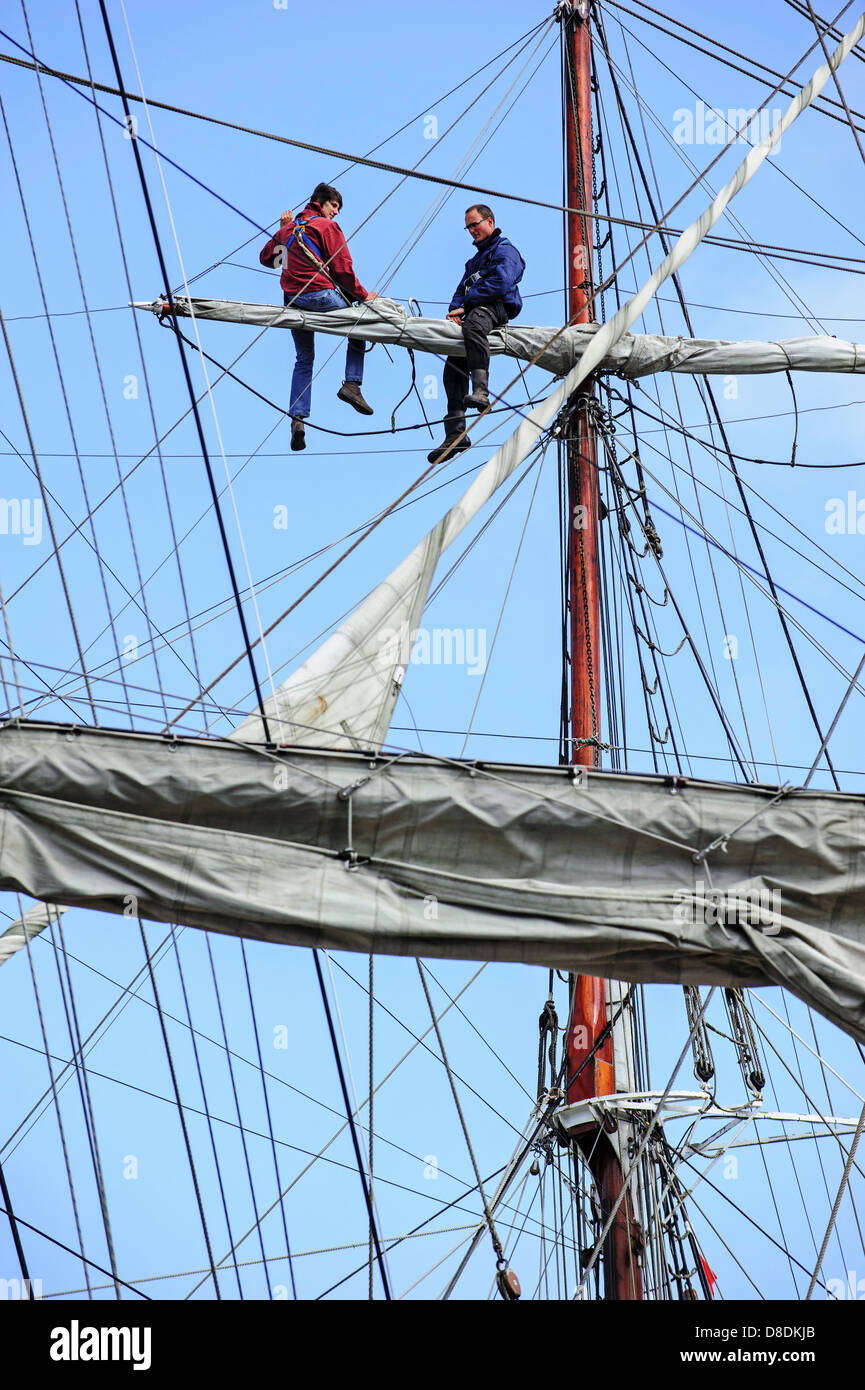 Two sailors sitting on yard of sailing vessel - Stock Image