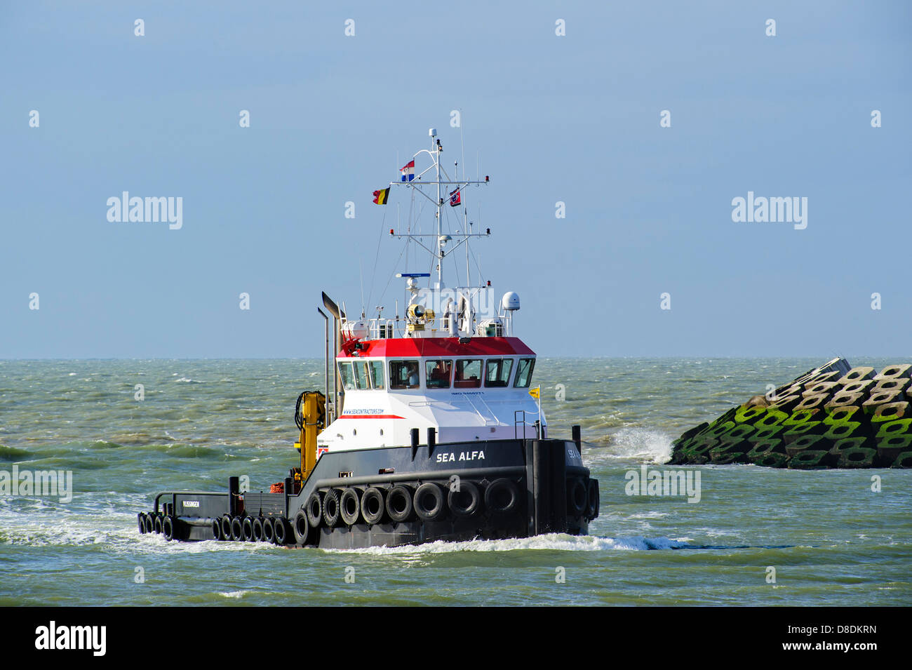 Tugboat Sea Alfa entering port on the North Sea, Netherlands Stock Photo