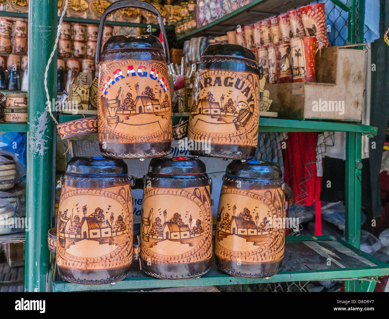 Tooled leather thermos bottles on display for sale at a vendor's stall in an open air market in Asunción. - Stock Image