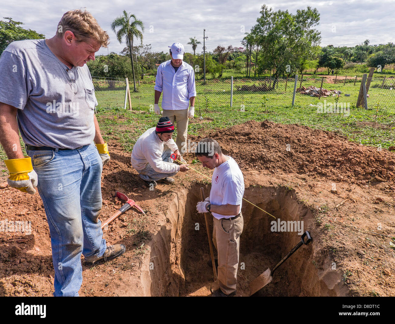 Four male workers, three Caucasians and one Hispanic take measurements as they dig a septic tank at a new home building - Stock Image