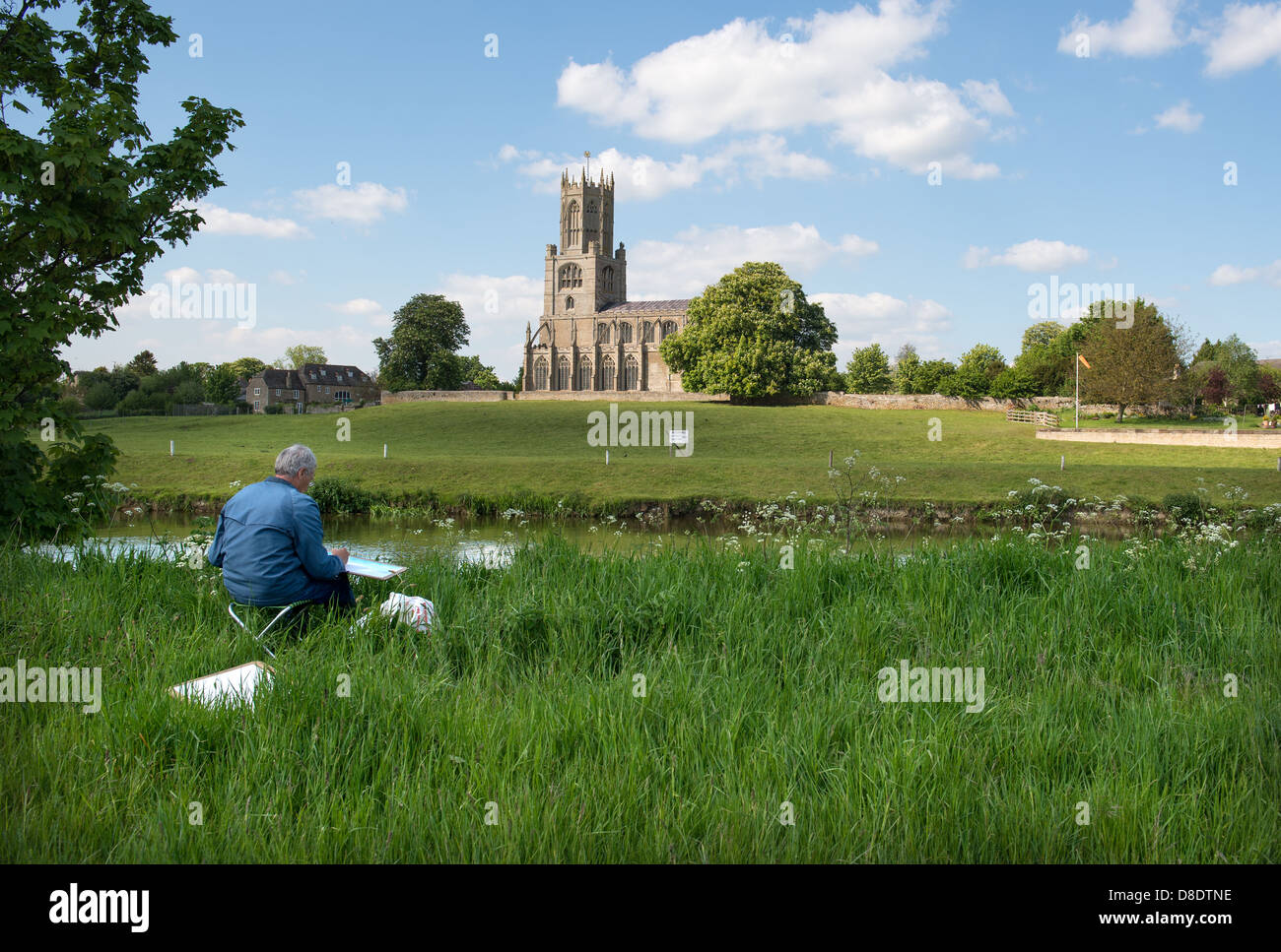 The Church of St Mary and All Saints, Fotheringhay in Northamptonshire with an artist in the foreground painting Stock Photo