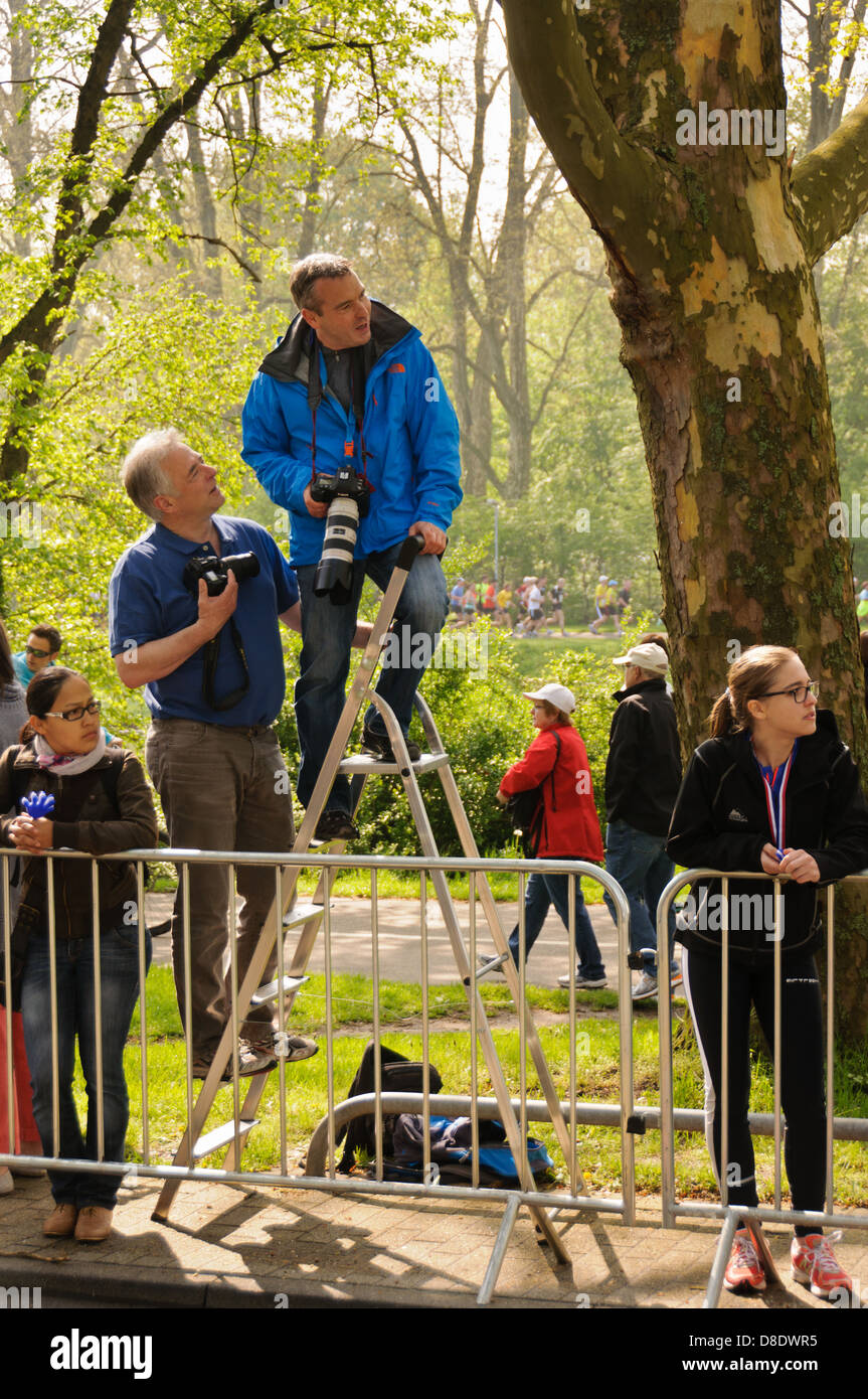 2 photographers with DSLR on a ladder, 2 female teenagers behind the barrier of a marathon run course – Heilbronn - Stock Image