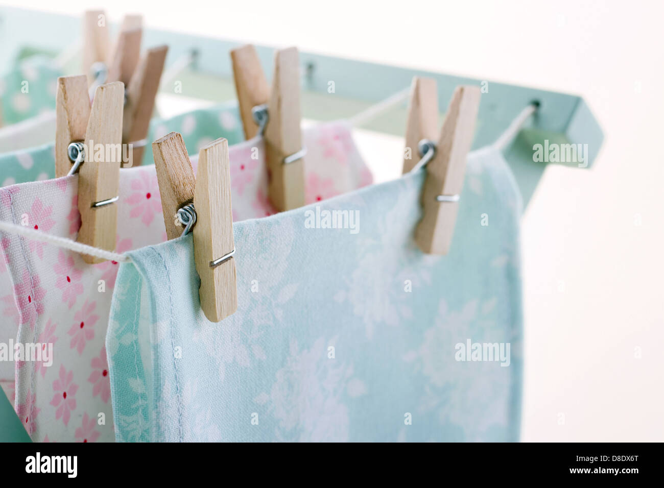 Closeup of pastel color laundry drying on vintage wooden drying rack with copy space - Stock Image