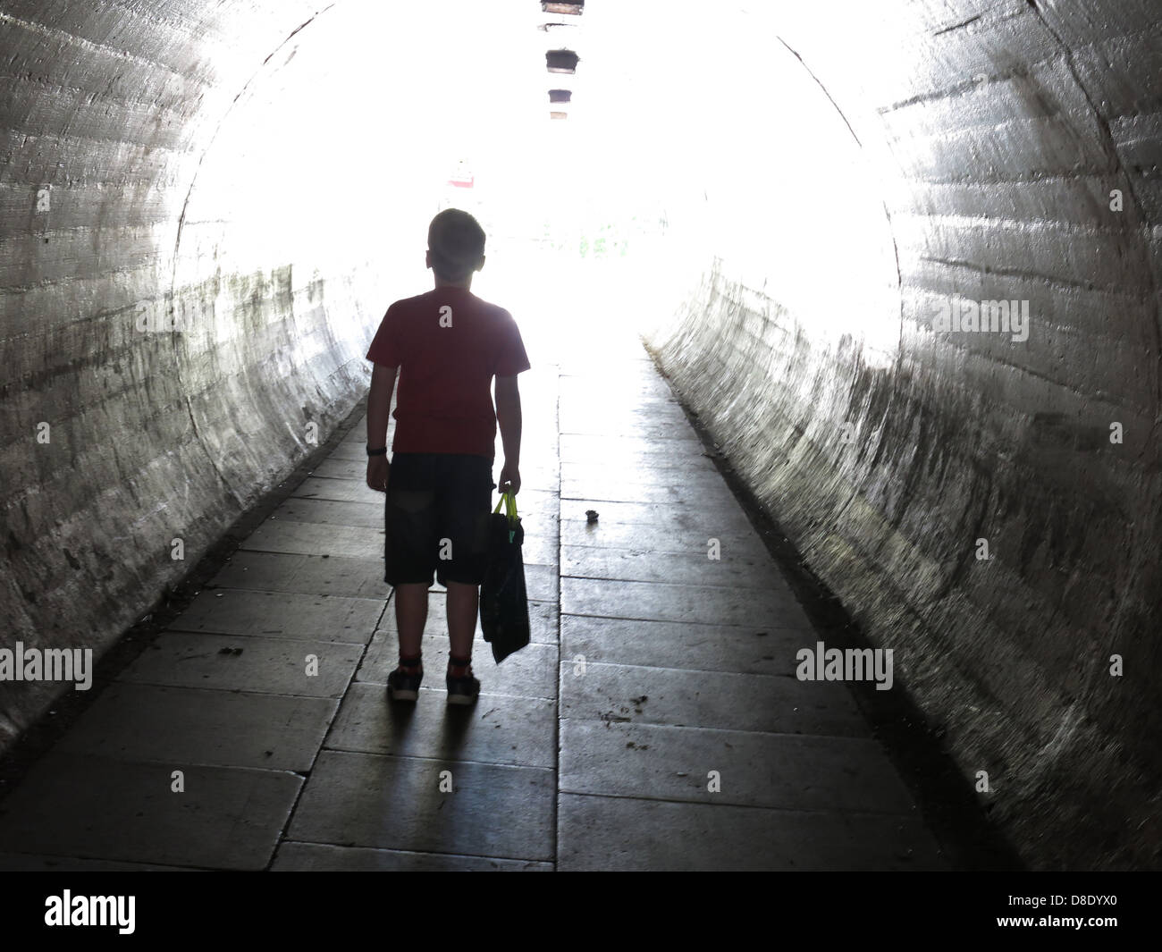 School child walking in a dark subway - Stock Image