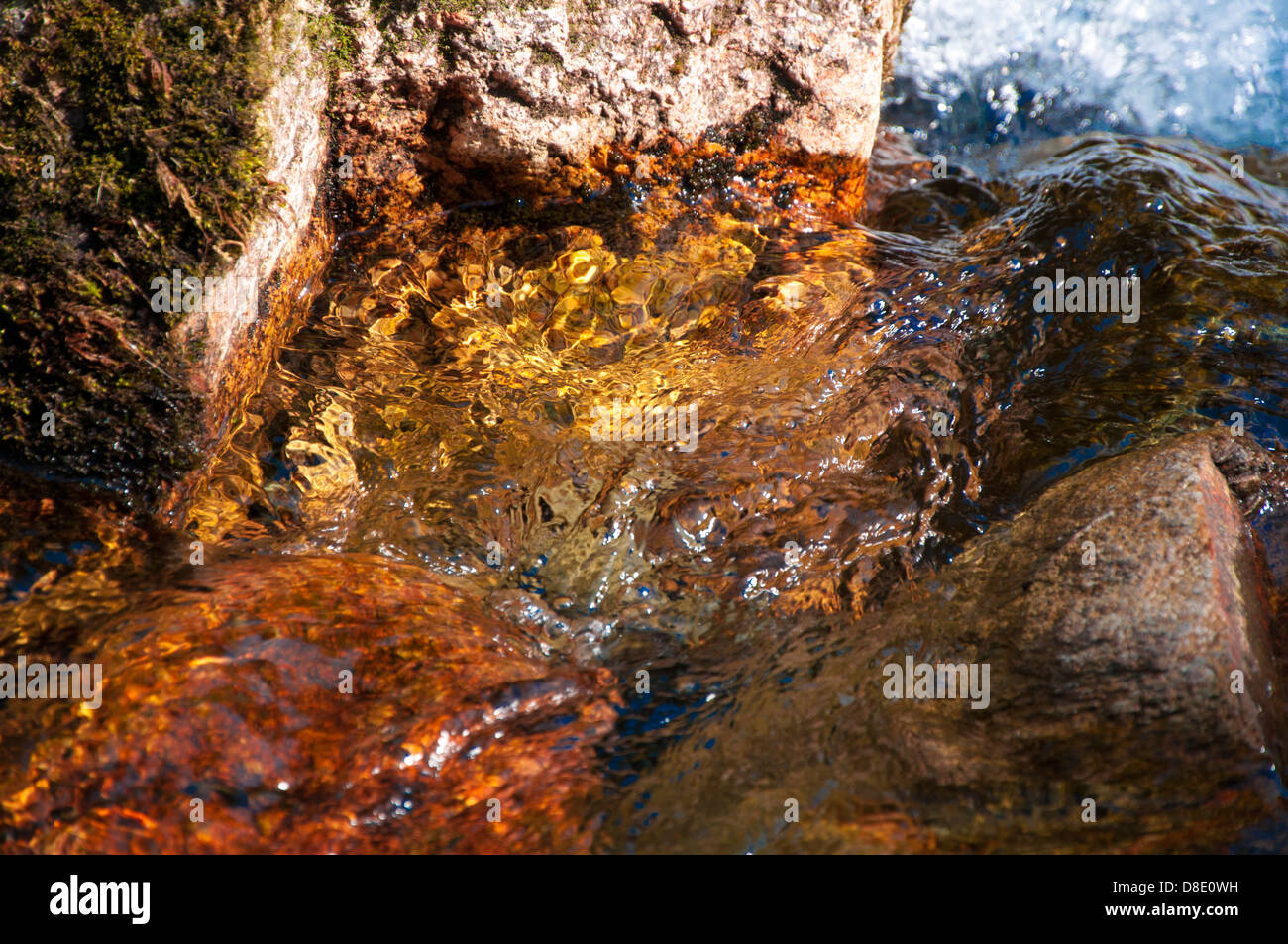 Crystal clear water flowing over golden rocks - Stock Image
