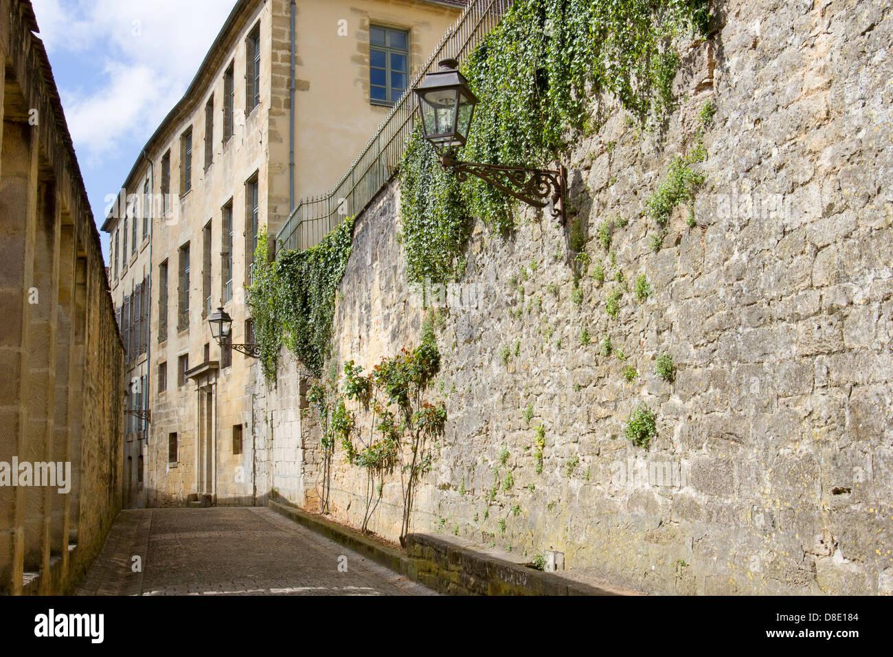 Ivy growing on medieval sandstone buildings along cobblestone street in charming Sarlat, Dordogne region of France - Stock Image