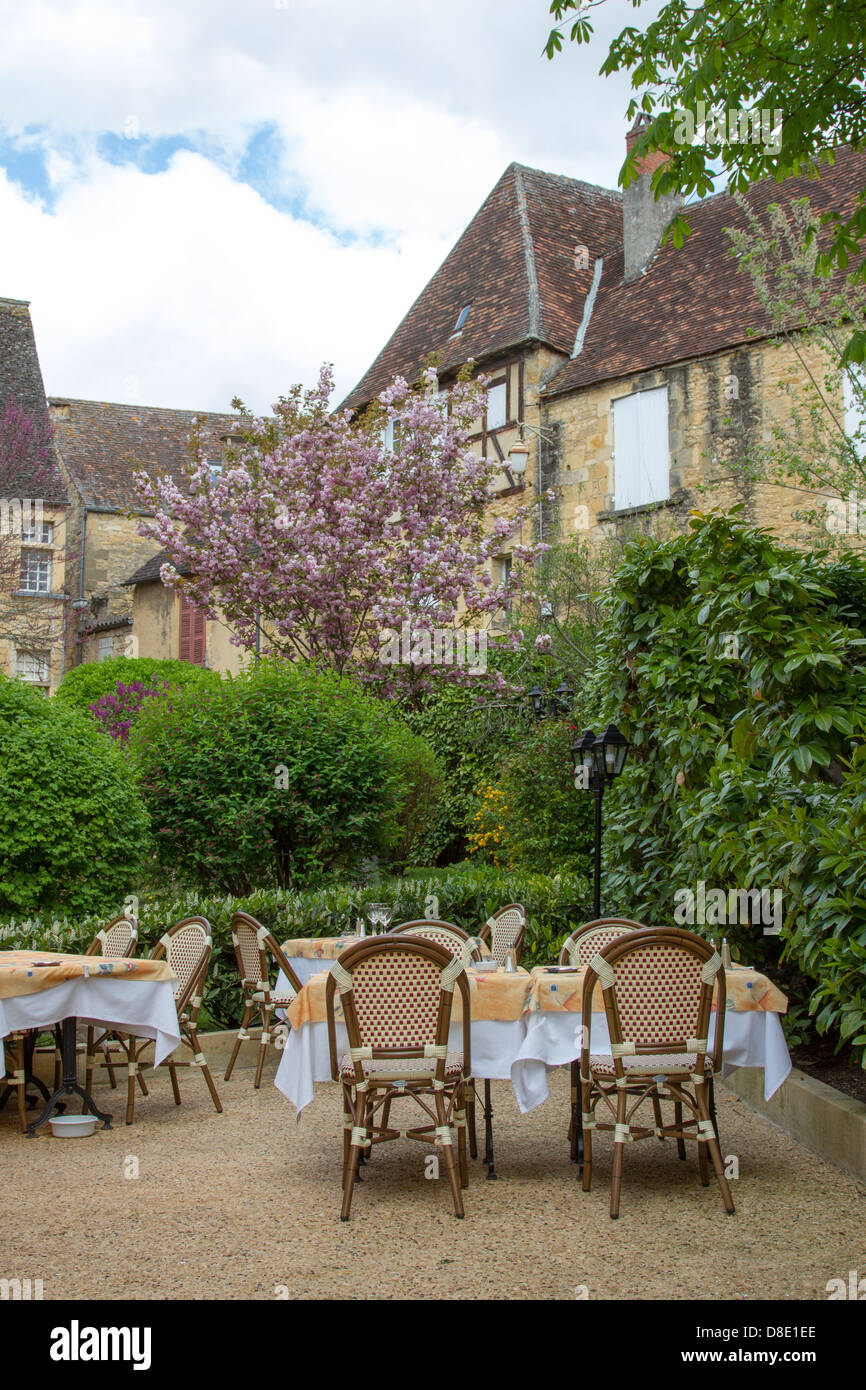 Outdoor courtyard dining at a restaurant by medieval sandstone buildings in charming Sarlat, Dordogne region of - Stock Image