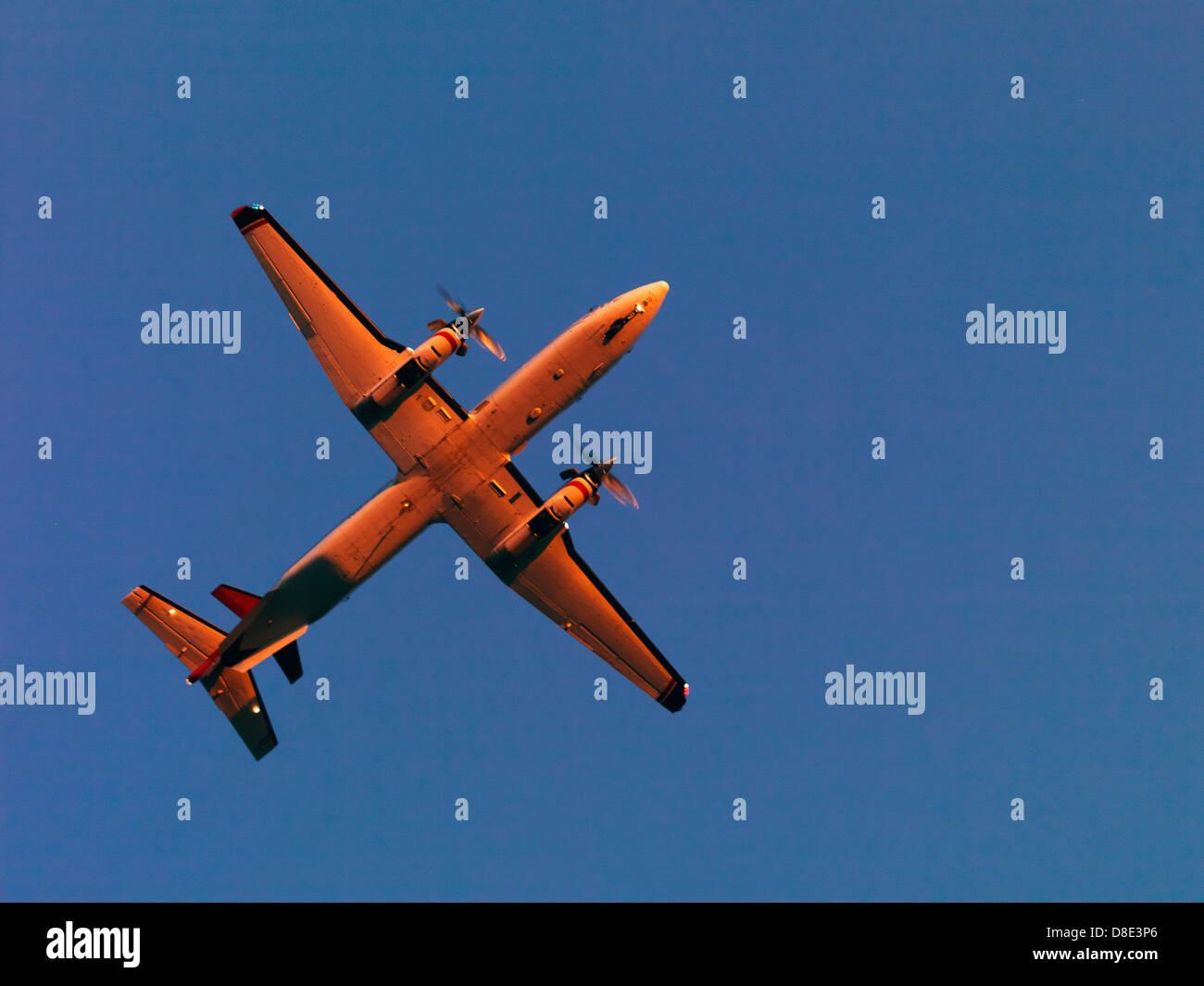 ERA Airlines beechcraft 1900D flying overhead into the sun set - Stock Image