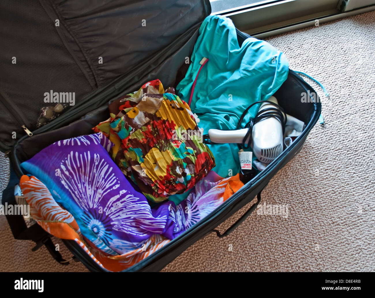 This is a suitcase packed with clothing and hair dryer, ready for a vacation concept, or travel. - Stock Image