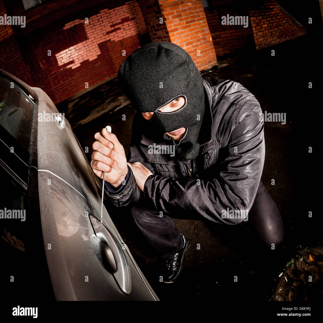 Robber and the car thief in a mask opens the door of the car and hijacks the car. - Stock Image
