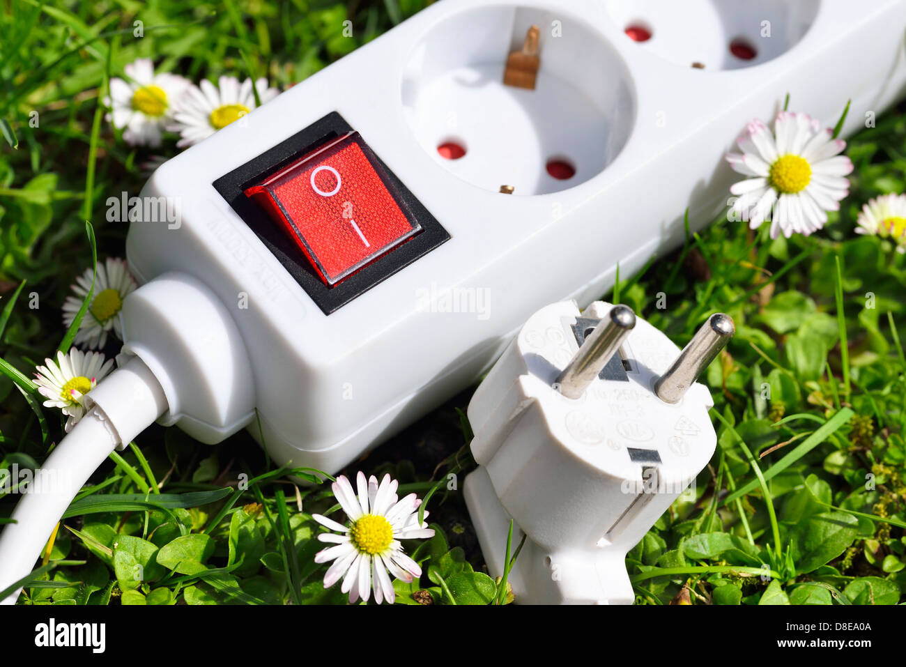 Outlet in grass, green energy symbol photo - Stock Image