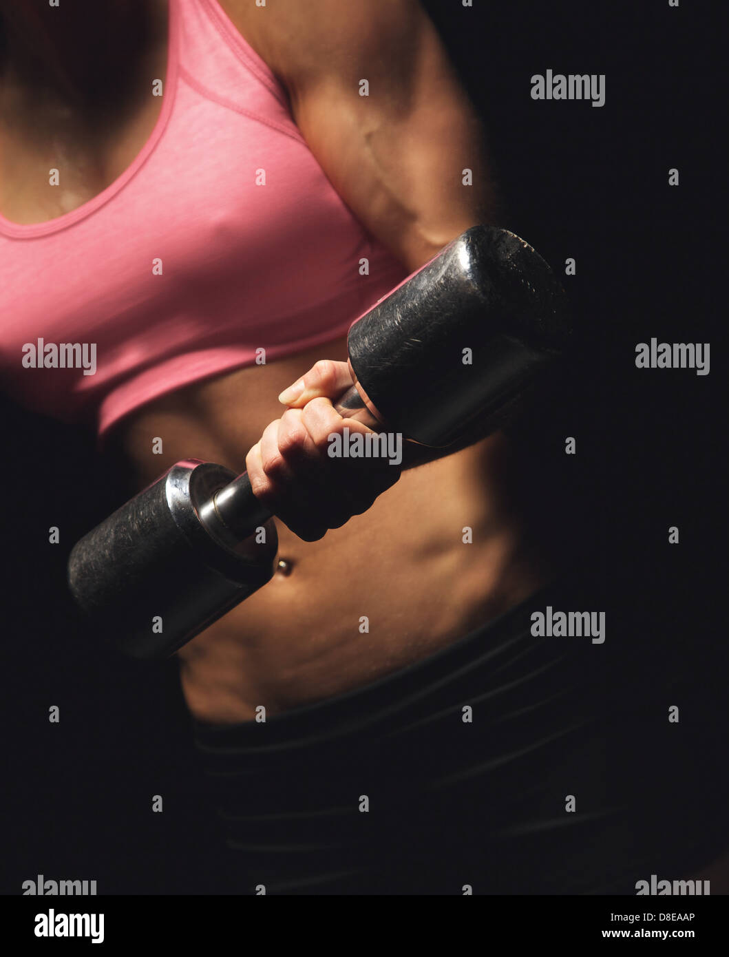 Torso of an active fitness woman doing a power workout with a dumbbell - Stock Image