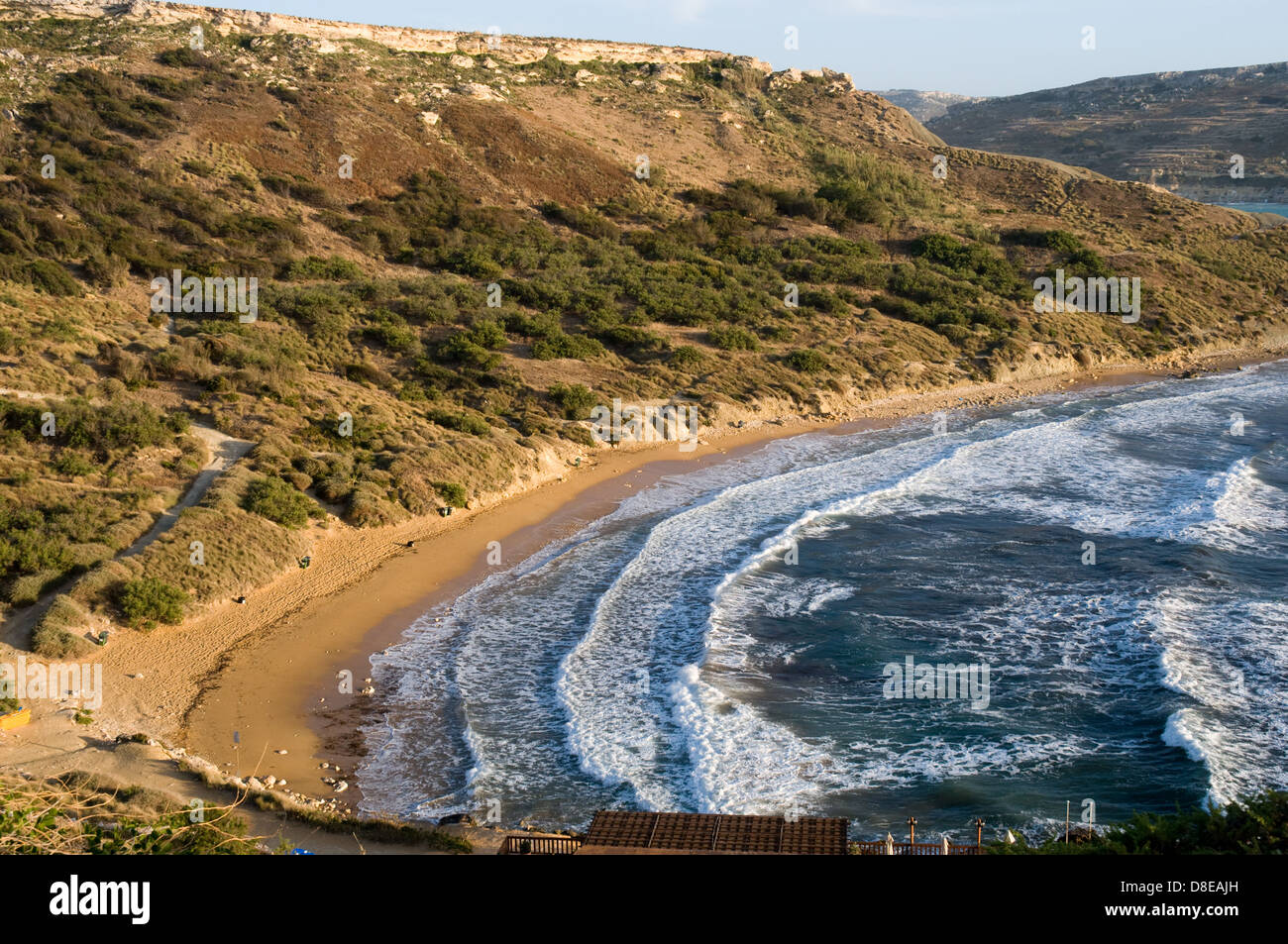 Strong winds drive large waves on to a deserted beach at Ghajn Tuffieha , Malta - Stock Image