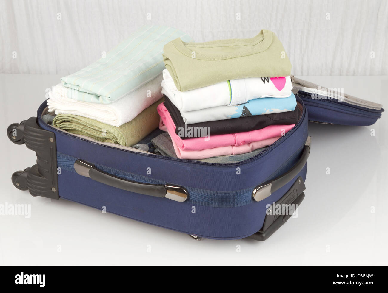 An opened suitcase packed with a lot of colorful cloths - Stock Image