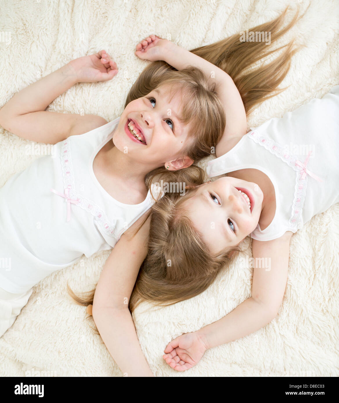 happy kids lying on back in pajamas top view - Stock Image