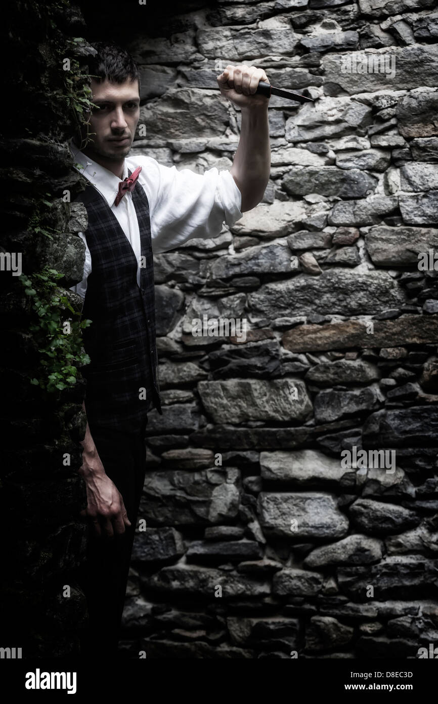 a man in a dark alley with a knife - Stock Image
