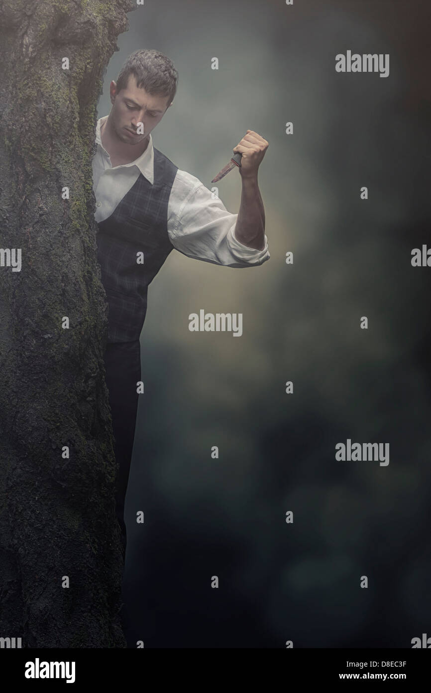 a man hiding behind a tree with a knife - Stock Image