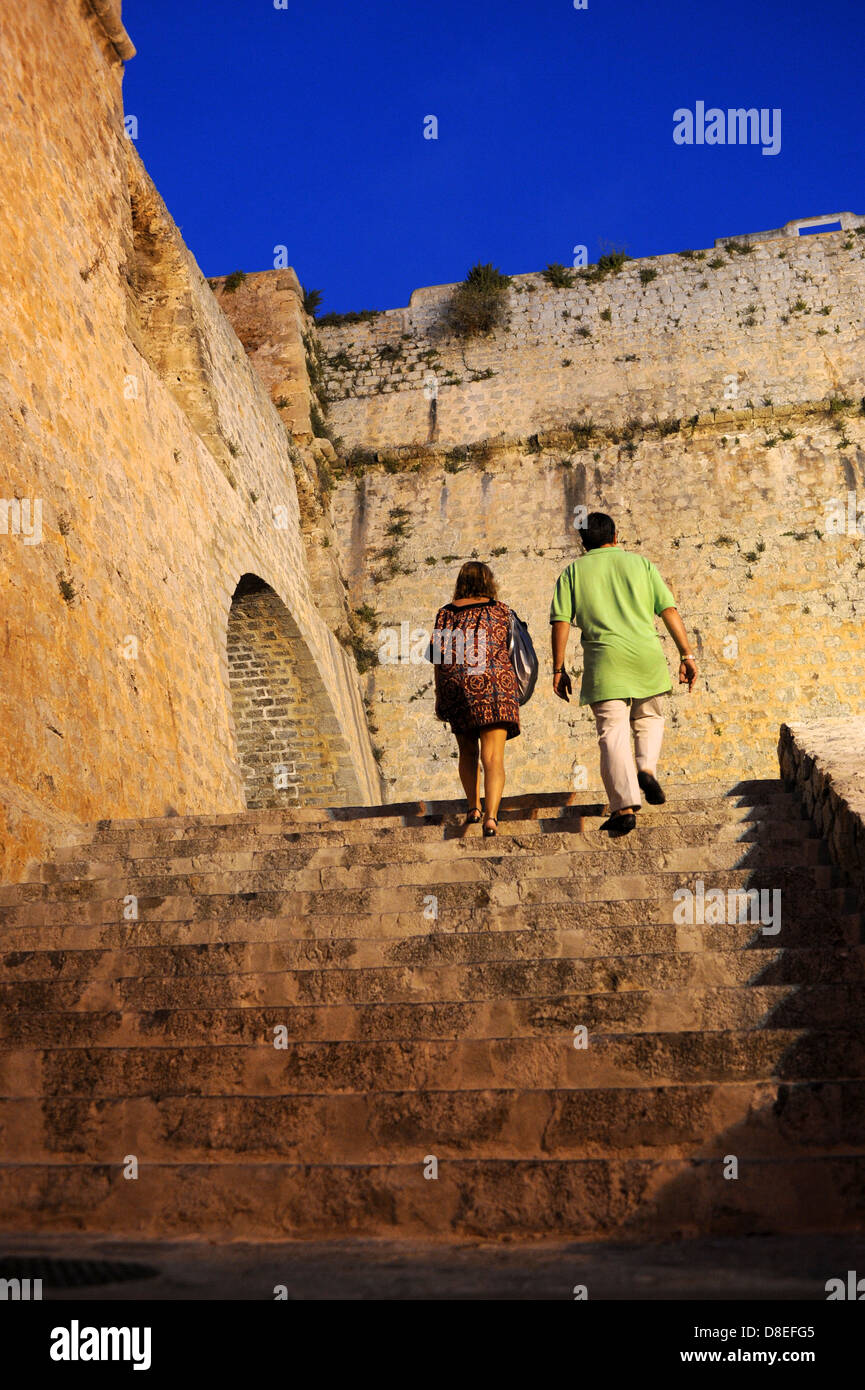 Holiday Makers walk up the steps to the castle district on a hot summer night in Ibiza Town. Stock Photo