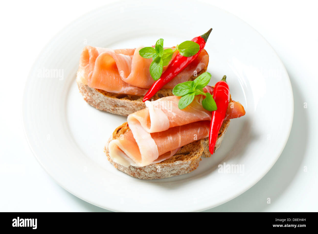 Prosciutto open faced sandwiches garnished with red chili peppers - Stock Image