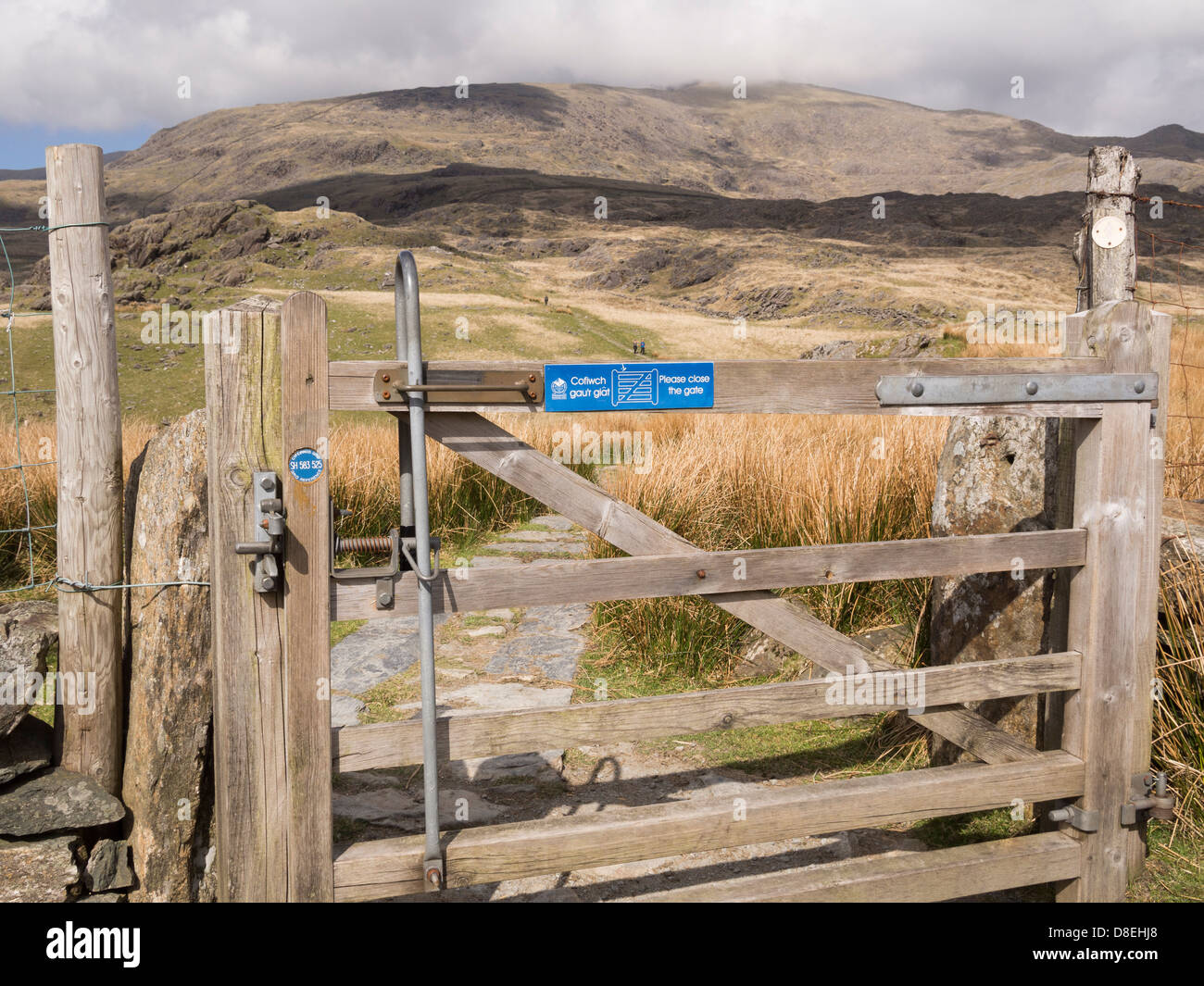 Gate with grid reference disc on Rhyd Ddu path up to Mt Snowdon with a view to the distant peak in Snowdonia, North - Stock Image