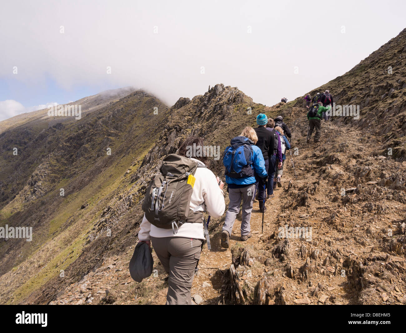 Ramblers walking on Rhyd Ddu path on Bwlch Main to Snowdon with view of peak shrouded in low cloud. Snowdonia North Stock Photo