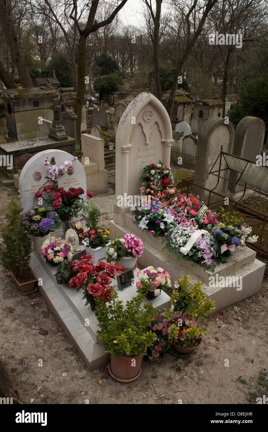 Parisian graveyard. Fresh wreaths of flowers laid on two graves in the Père Lachaise cemetery, the largest of the Stock Photo