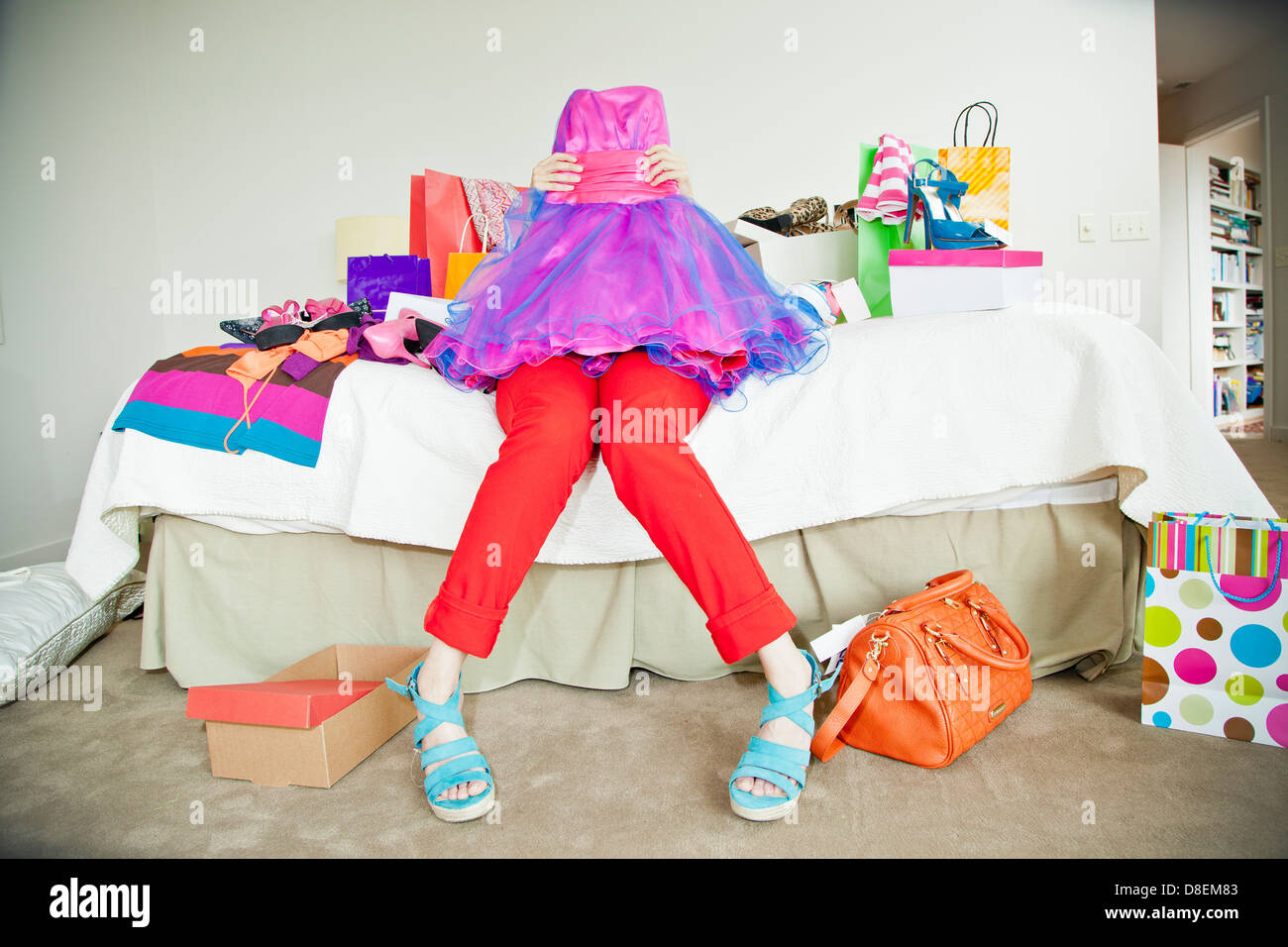 Woman on bed surrounded by shopping bags Stock Photo