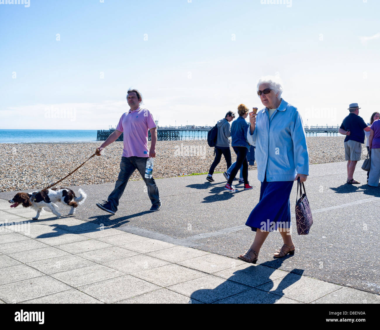 An elderly woman walks along a promenade eating an Ice cream on a hot day. Picture by Julie Edwards - Stock Image