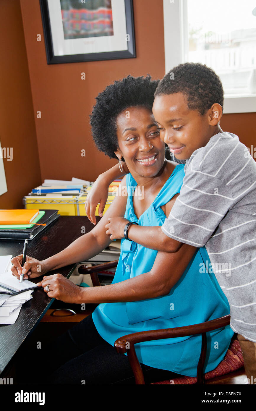 Woman working at home office with son Stock Photo