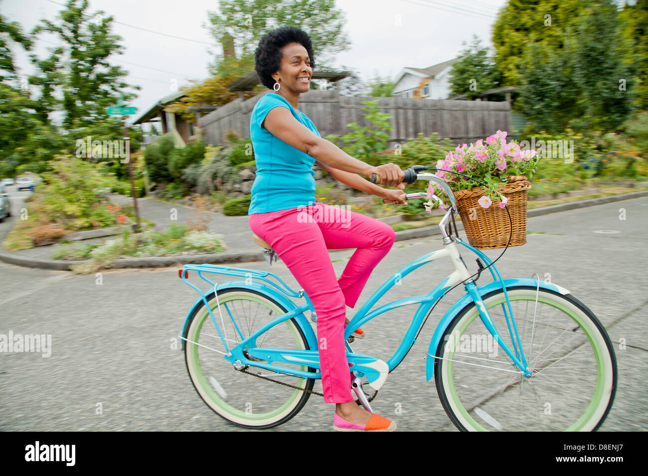 Woman riding retro bicycle with flower basket Stock Photo