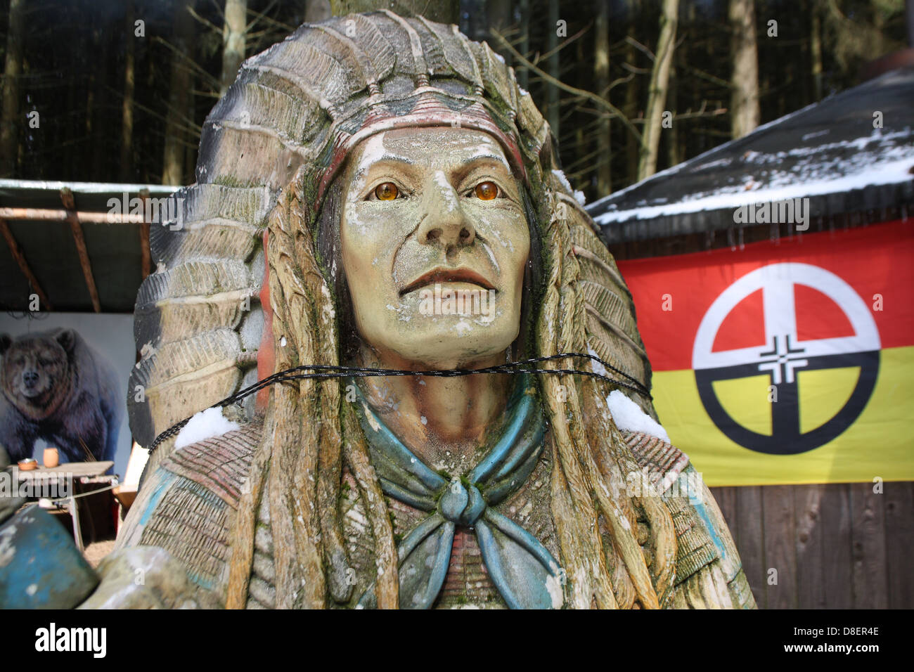 A wooden depiction of a West Indian wearing a feather headdress. - Stock Image