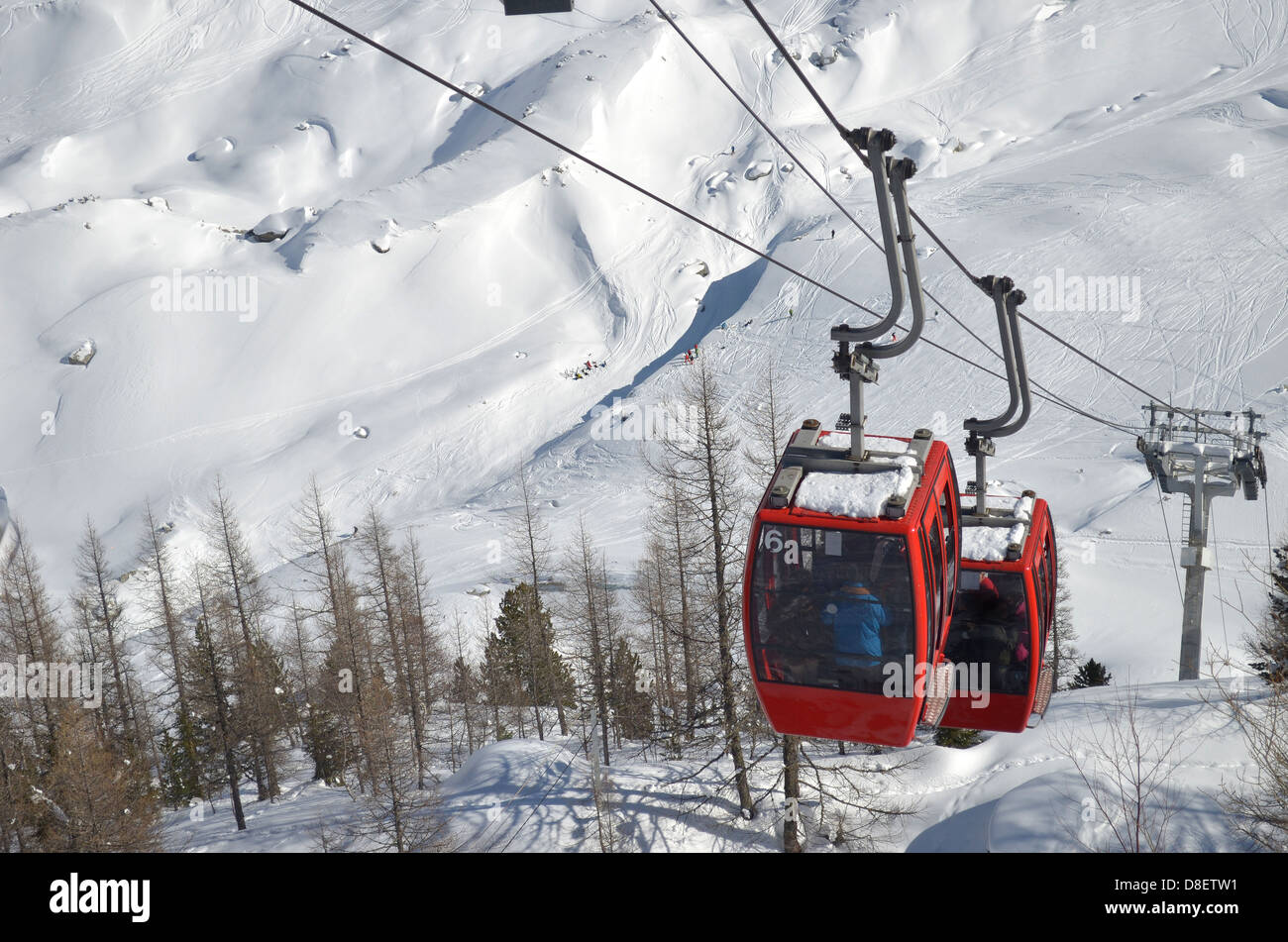 Two red cablecars climbing snow covered mountain, seen from above Stock Photo
