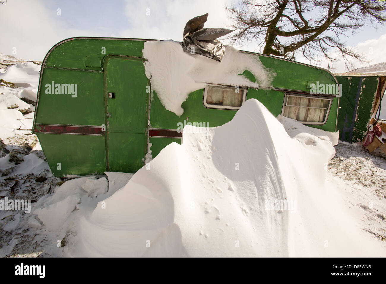 A caravan snowed in by large snow drifts during the extreme weather event of late March 2013 - Stock Image